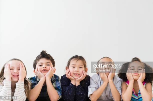 Children resting chins in hands