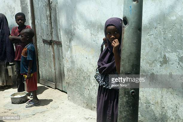 Children returning from a feeding center with metal cans filled with foodThousands of the poor in Mogadishu rely on food from feeding centers run by...