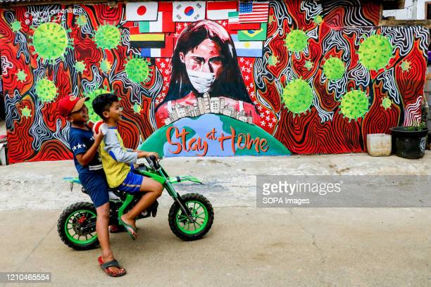 Children ride a bicycle past a coronavirus awareness graffiti during a lockdown. Indonesian local artists drew murals on the walls of the houses for...