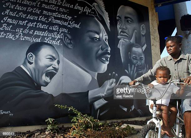 Children ride a bicycle past a mural in honor of the slain civil rights leader Martin Luther King Jr January 21 2002 in Miami Florida