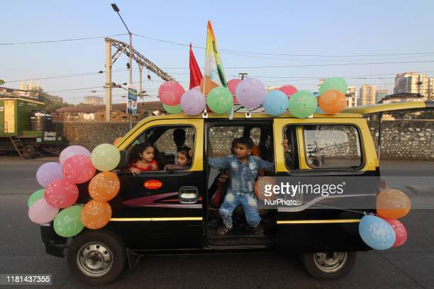 Children ride a taxi decorated with balloons during a religious processions to celebrate Prophet Muhammad's birthday in Mumbai India on 10 November...