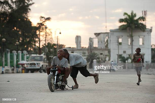 Children ride a toy motorcyle at a make shift camp across from the National Palace in PortAuPrince April 12 2011 The 72 earthquake in Jan of 2010...