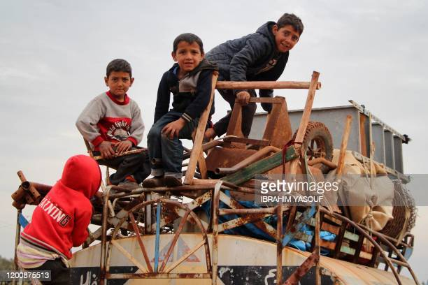 Children ride atop a water truck that is also loaded with furniture in the countryside of the village of Saharah, lying on the western edge of...
