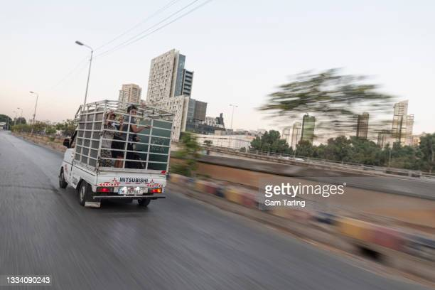 Children ride in a truck with their father to work selling shoes at a market, in Beirut, Lebanon, on August 14, 2021. Lebanon's economic crisis has...