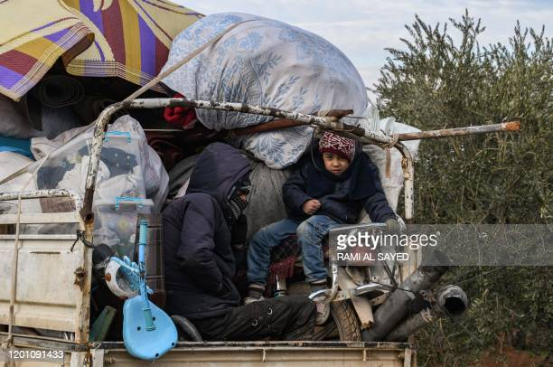 Children ride in the back of a truck passing through the town of Jindayris near the Syrian-Turkish border, west of the city of Afrin in the west of...