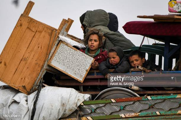 Children ride in the back of a truck with furniture, mattresses, and blankets while passing by an internally-displaced persons camp by Dayr Ballut...