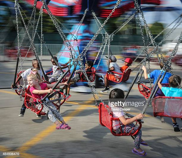 Children ride on a swing carousel as families have fun on the kids midway rides at the Canadian National Exhibition