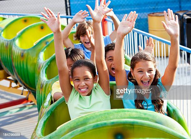 Children riding a green roller coaster
