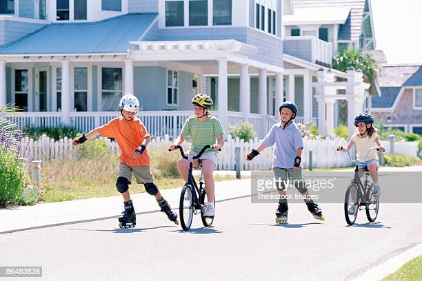 Children riding bicycles and inline skating down street