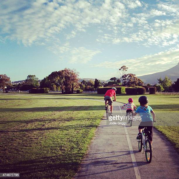 Children riding bicycles with father along walkway
