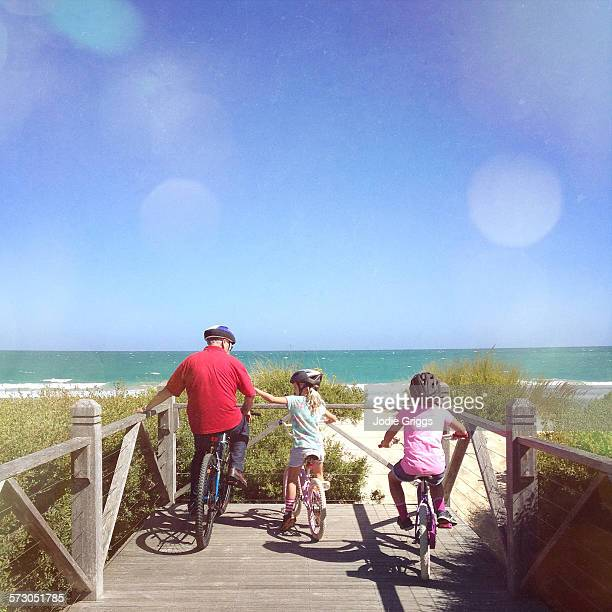 Children riding bike with grandfather at the beach