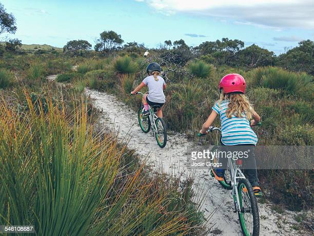 Children riding bikes on sandy track with father