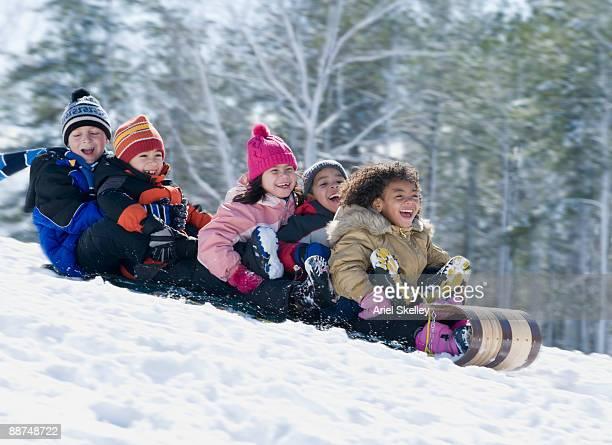 Children riding downhill on sled