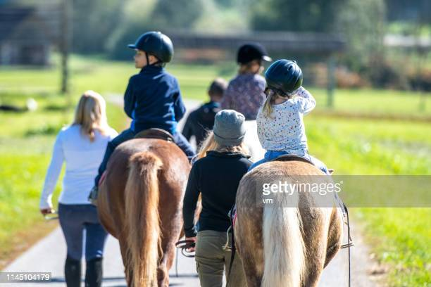 children riding in a park - horseback riding stock pictures, royalty-free photos & images