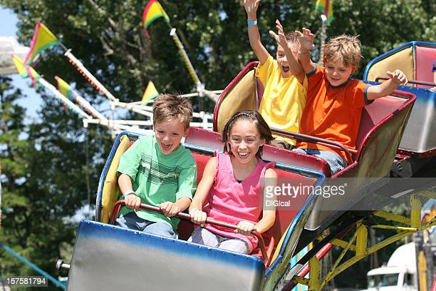 children riding on a roller coaster - amusement park ride stock pictures, royalty-free photos & images