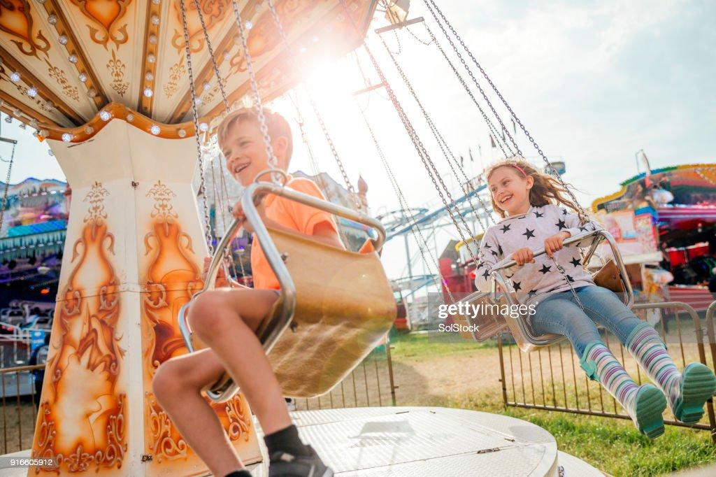 見本市会場でブランコに乗る子供たち : ストックフォト