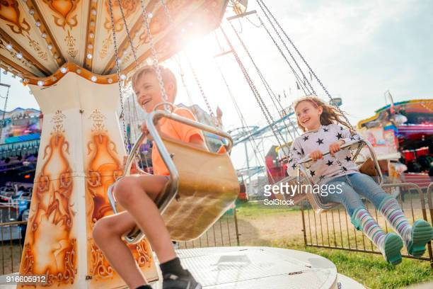 children riding on the swings at the fairground - traveling carnival stock pictures, royalty-free photos & images