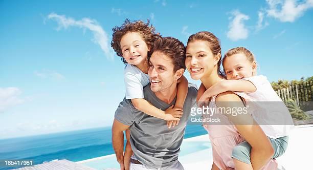 Children riding piggyback with parents at a beach