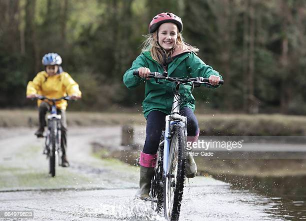 children ringing over ford on bikes - sporting term stock pictures, royalty-free photos & images