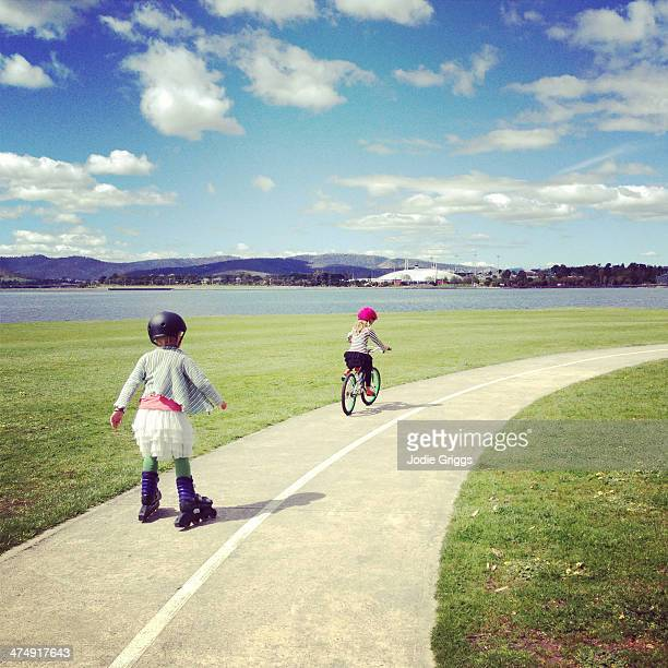 Children roller blading and riding along footpath