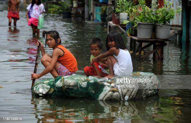 Children row a makeshift raft through flood waters caused by a passing typhoon in Malabon Metro Manila on June 21 2011 Philippine Atmospheric...