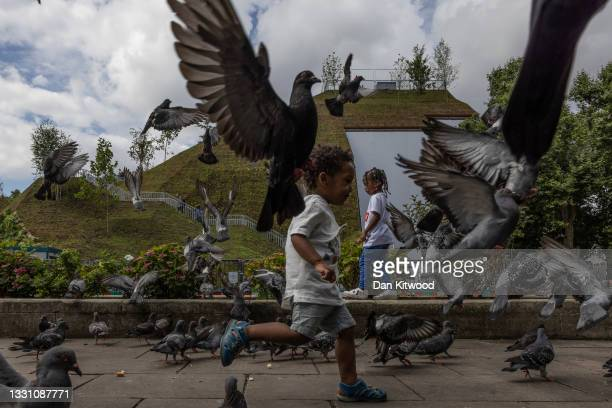 Children run around amongst pigeons in front of the 'Marble Arch Mound' on July 28, 2021 in London, England. The temporary installation next to...