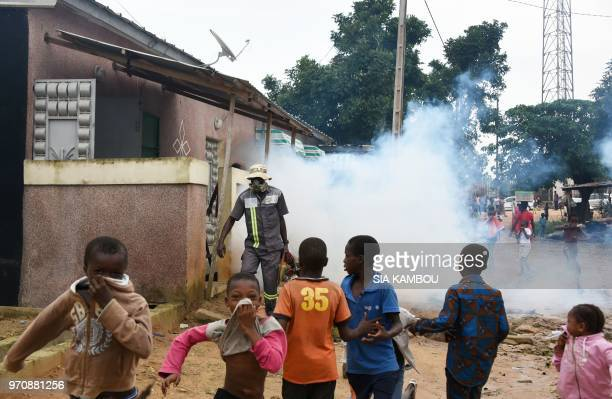 Children run as an agent of the National Institute of Public Hygene carries out fumigation in the Anyama district of Abidjan on June 9 as part of the...