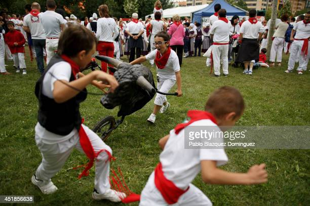 Children run in front of a toy bull after the Encierro Txiki on the third day of the San Fermin Running Of The Bulls festival on July 8 2014 in...