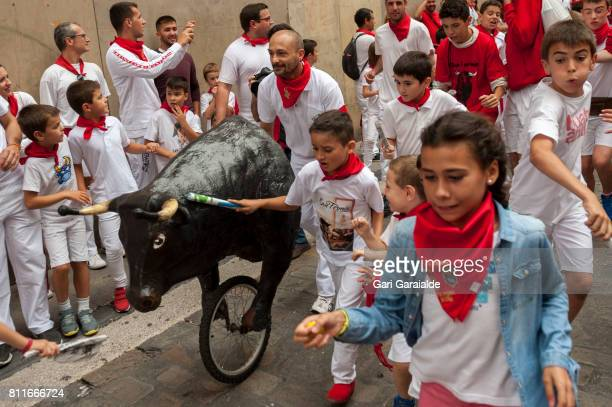 Children run in front of a toy bull during the Encierro Txiki during the fifth day of the San Fermin Running of the Bulls festival on July 10 2017 in...