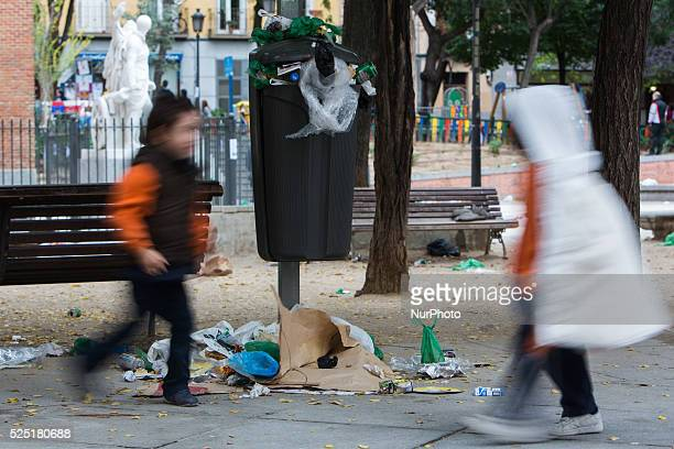 Children run in front of an overflowing trash bin during the fourth day of a garbage collectors strike in Madrid Spain Street cleaners trash...