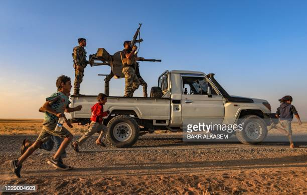 Children run past a gun-mounted truck manned by Turkey-backed Syrian fighters near the rebel-controlled town of Tal Abyad in the northern Syria's...
