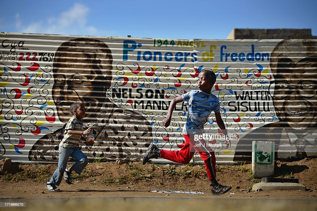 Children run past a mural of former South African president Nelson Mandela and other freedom fighters in the Orlando District of Soweto Township on June 30, 2013 in Johannesburg, South Africa. People continue to gather and lay flowers and tributes outside the Mediclinic Heart Hospital where Mandela is being treated for a lung infection on his 23rd day in hospital.