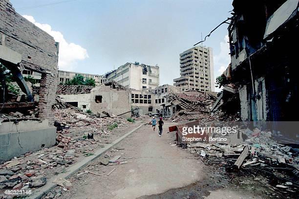 Children run through the NATO bomb damage in Pristina Kosovo