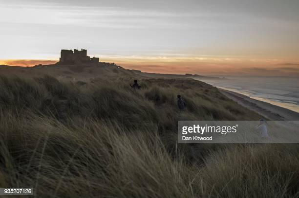 Children run through the sand dunes as the sun sets behind Bamburgh Castle on March 20 2018 in London England