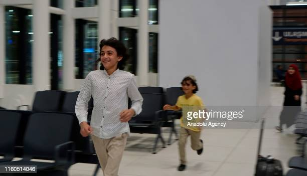 Children run to welcome Amine el Mulhim , a partially-sighted woman, following her release from Adra Prison in Damascus on August 09, 2019 in...