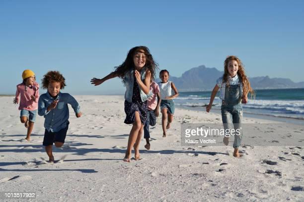 children running and laughing together on the beach - fugir da realidade imagens e fotografias de stock