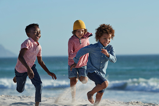 Children running and laughing together on the beach - gettyimageskorea