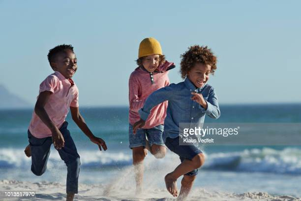 Children running and laughing together on the beach