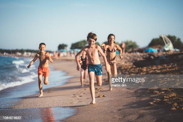 children running and shooting with water pistols on the beach - bulgaria stock pictures, royalty-free photos & images