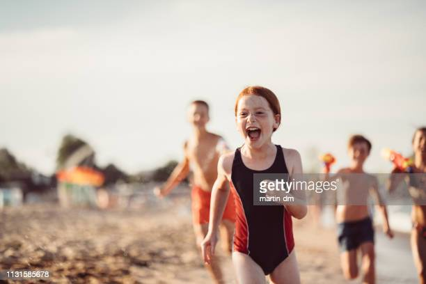 children running and shooting with water pistols on the beach - redhead stock pictures, royalty-free photos & images