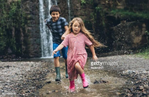 Kinder laufen an einem Fluss