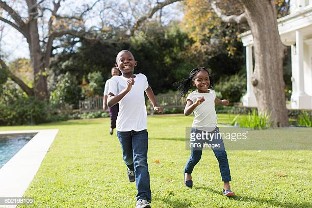 Children (6-7, 8-9) running in backyard, Cape Town, South Africa