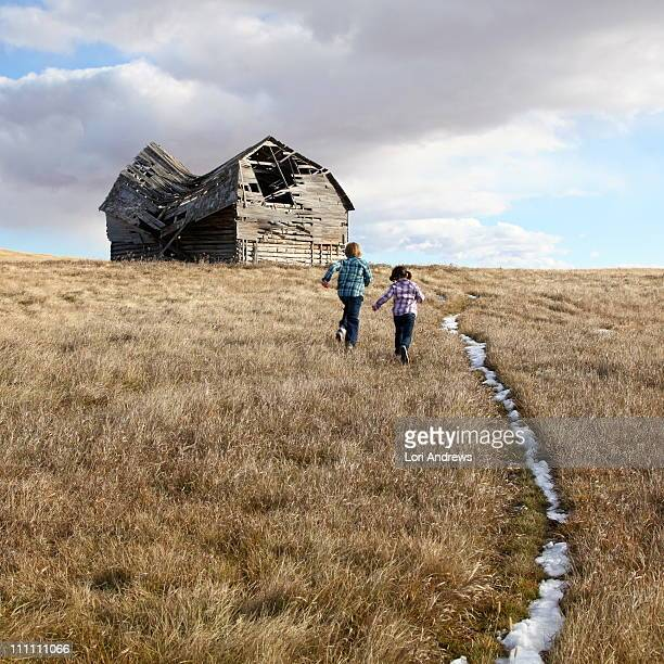 Children running in country with barn