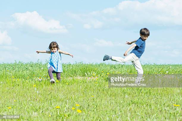 Children running in field with arms out