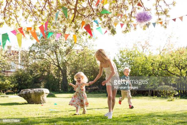 children (18-23 months, 4-5, 8-9) running in garden - 18 23 months stock pictures, royalty-free photos & images