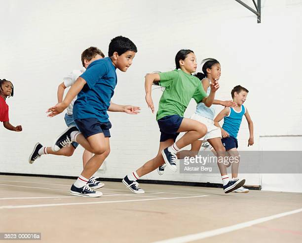children running in gymnasium - physical education stock pictures, royalty-free photos & images