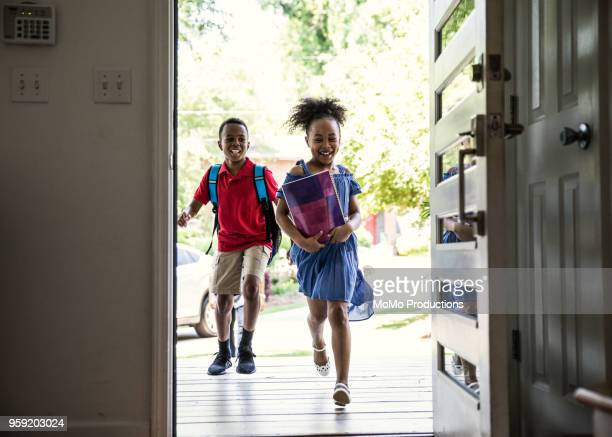 children running into home after school - girl shoes stock pictures, royalty-free photos & images