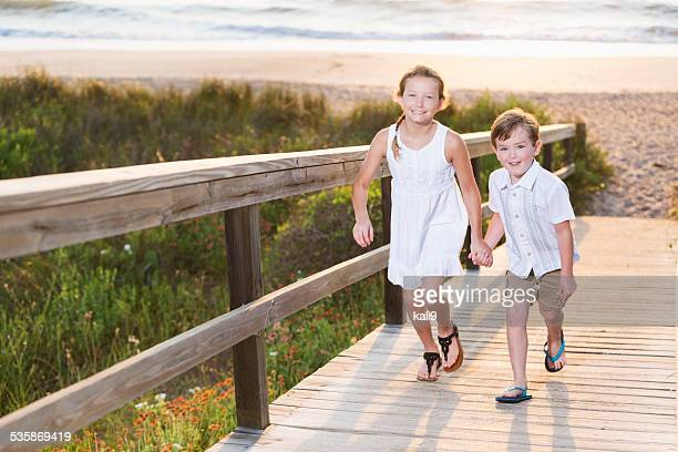 children running on beach boardwalk - lane sisters stock photos and pictures
