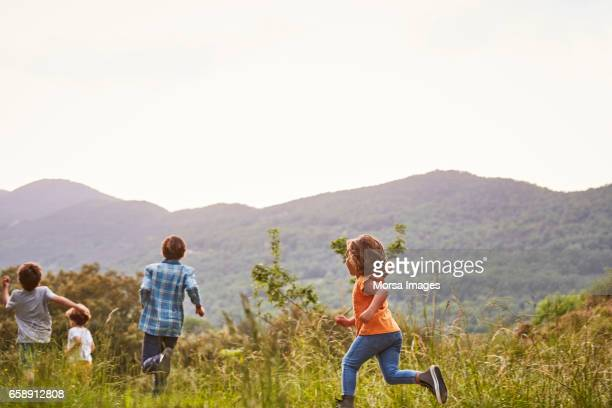 children running on grassy field against clear sky - catalonia stock pictures, royalty-free photos & images