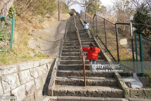Children running on long steps to a mountain